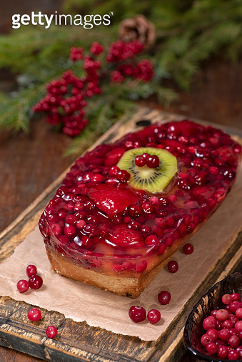 Christmas cake with jellied cranberries and fruits on the board.