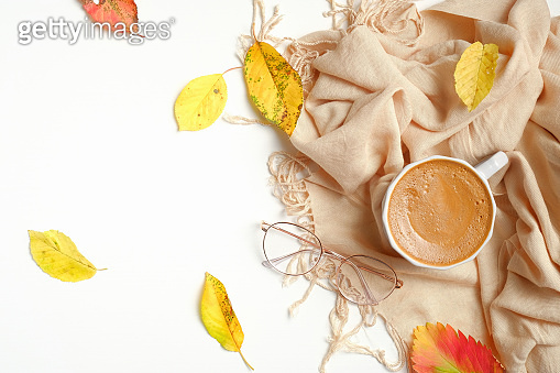 Autumn flat lay composition. Morning cup of coffee, beige female scarf, fallen leaves on white wooden background. Autumn, fall concept. Top view, overhead.