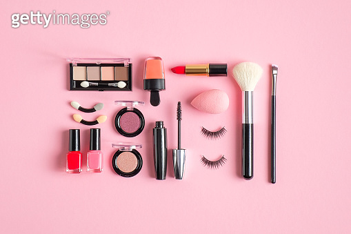 Makeup cosmetic kit. Flat lay composition with lipstick, nail polish, make-up brush, nude eyeshadow palette, false eyelashes on pastel pink background. Makeup artist tools and beauty products set