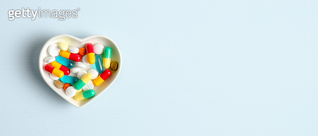 Colorful medical pills capsule in Heart shaped plate on yellow background. Top view with copy space. Healthcare, pharmacy, medicine concept. Drugstore banner design template