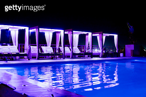 Luxury hotel's tanning beds in pavilion by the swimming pool at night