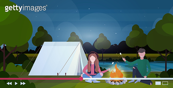 hikers bloggers roasting marshmallow candies on campfire recording video man woman vloggers live streaming blogging hiking concept landscape background horizontal full length