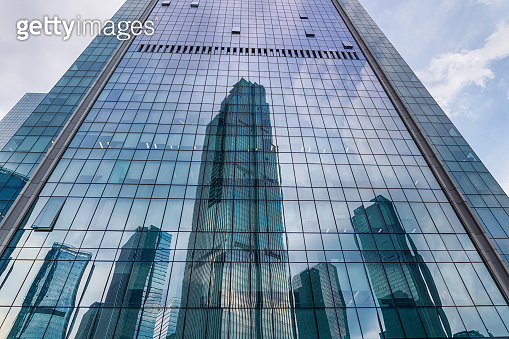 low angle view of modern skyscrapers reflect on office building exterior
