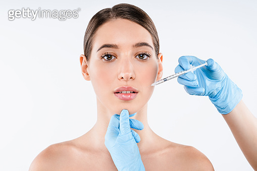 Close up of beautiful woman gets injection in her lips isolated over white background