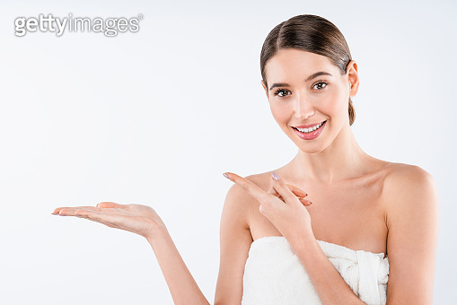 Young beautiful woman wearing towel after shower over isolated white background pointing