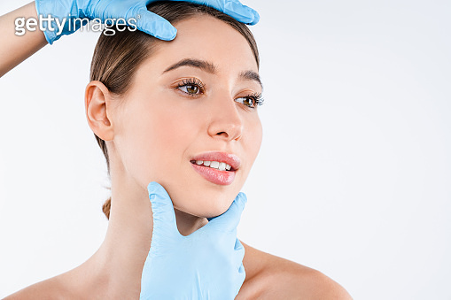 Plastic surgeon checking face of young woman over white background
