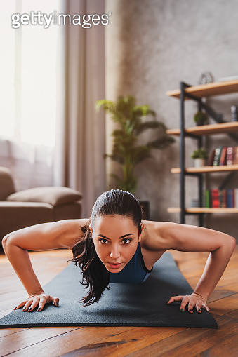 Vertical shot of beautiful young sport lady doing push ups while workout at home