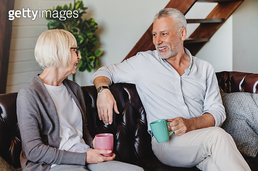 Happy mature couple or friends drinking coffee while resting on couch at home