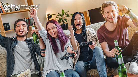 Group of multi ethnic young friendsplaying in video games at home while drinking beer