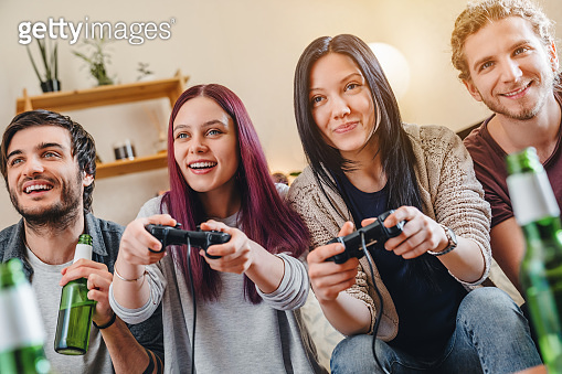 Happy cheerful friends playing video game with beer at home