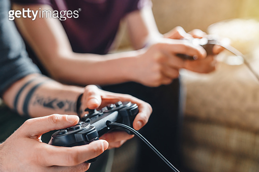Close up of unrecognizable friends in casual clothing using joysticks while having fun with video game at home