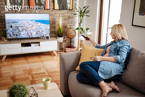 Mature barefoot woman with legs on couch watching interesting TV program