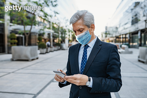 Essential worker - businessman in suit with face mask during lockdown using smart phone
