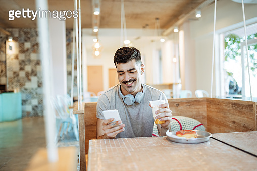 One millennial Latino man eating snack and using phone for messaging and e-banking