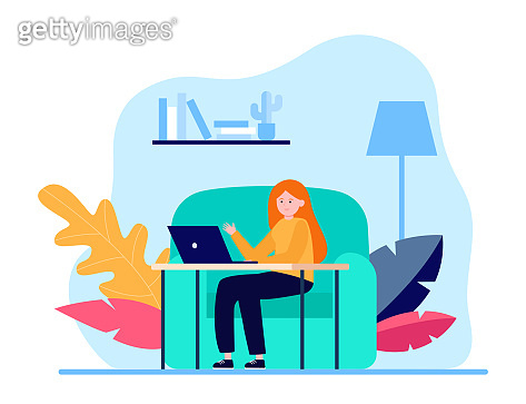 Young woman sitting at sofa and working via laptop
