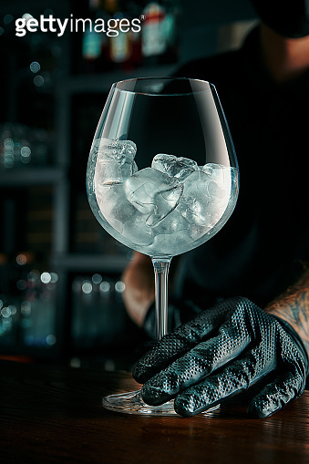 The bartender prepares an alcoholic cocktail. The process of creating a drink in a beautiful glass