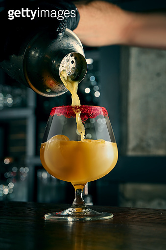 The bartender prepares an alcoholic cocktail. The process of pouring orange liquid from a shaker into a beautiful glass with ice at the bar. Bar accessories