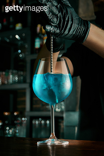 The bartender prepares an alcoholic cocktail. Stirring liquid into a beautiful glass with ice at the bar. Bar accessories
