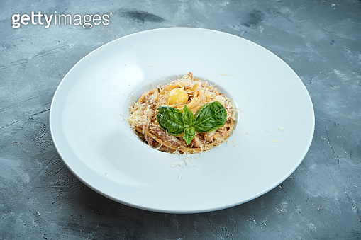 Italian pasta carbonara with yolk, bacon and parmesan cheese in a white plate on a gray background