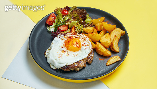 Beef steak with fried eggs with a side dish of salad and fried potatoes on a black plate on a colored background. Appetizing food for lunch