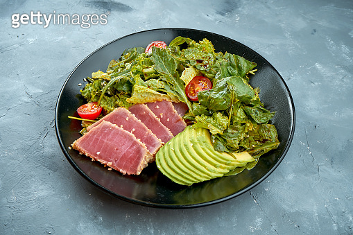 Salad with tuna, avocado and cherry tomatoes in a black plate on a gray background. Close up.