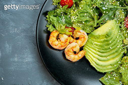 Salad with shrimps, avocado and cherry tomatoes in a black plate on a gray background. Top view. Half of plate