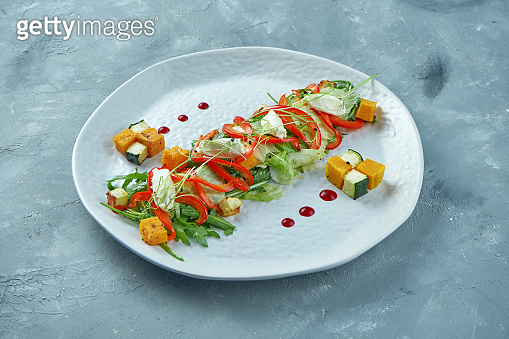 Asian style vegetarian salad with arugula, tomatoes, oranges and lettuce leaves on white plate on gray concrete background