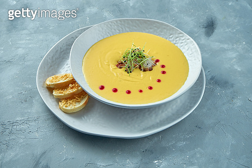 Pumpkin cream soup with octopus and croutons in a white bowl on a gray background. Creamy seafood soup