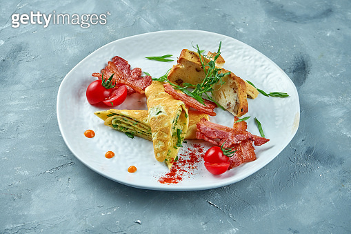 Perfect breakfast - scrambled eggs with spinach, bacon and fresh bread in a white plate on a gray background. Tasty omelet