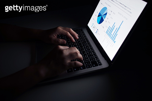 Hands are using laptop financial graph displays in dark rooms.