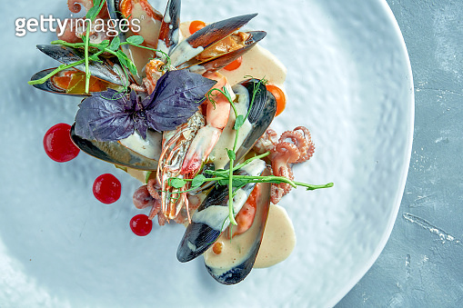 Seafood stewed in a creamy sauce. Mussels, baby octopus and shrimps with sauce in a white plate on a gray background
