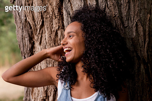 portrait outdoors of a beautiful young afro american woman smiling at sunset. Brown tree background. Lifestyle