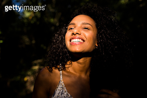 portrait outdoors of a beautiful young afro american woman smiling at sunset. Black background. Lifestyle