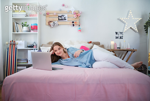 Beautiful happy young girl with laptop sitting and smiling, online dating concept.