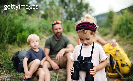 Family with small children hiking outdoors in summer nature, sitting and resting.