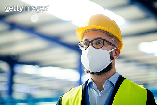 Technician or engineer with protective mask and helmet standing in industrial factory.