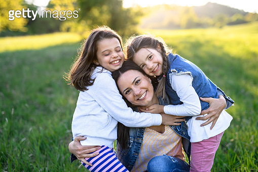 Mother with two small daughters having fun outdoors in spring nature, hugging.