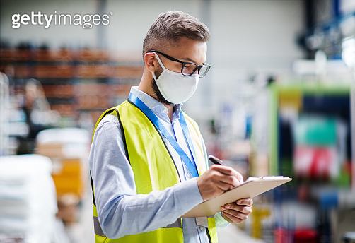 Technician or engineer with protective mask working in industrial factory, writing.