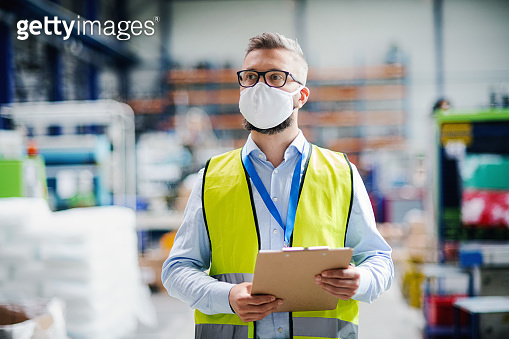 Technician or engineer with protective mask working in industrial factory, walking.