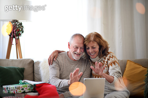Senior couple indoors at home at Christmas, having video call with family.