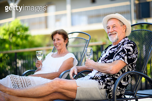Senior couple holding wine outdoors on holiday, relaxing.