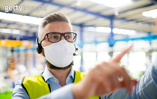 Technician or engineer with protective mask working in industrial factory.