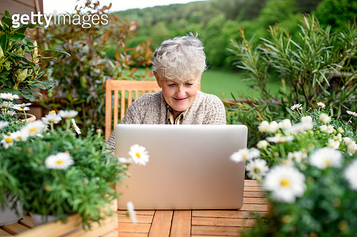 Senior woman with laptop sitting on terrace in summer, resting.
