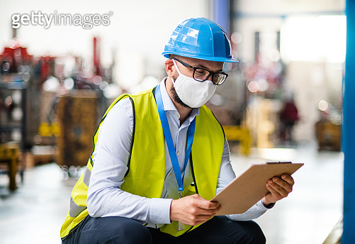 Technician or engineer with protective mask and helmet working in industrial factory.