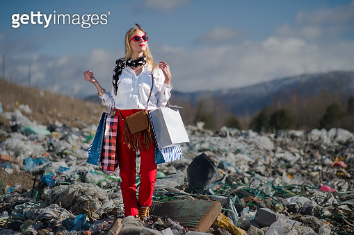 Modern woman on landfill, consumerism versus pollution concept.