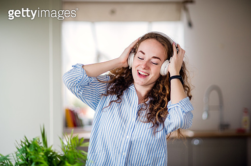 Young woman with headphones relaxing indoors at home.