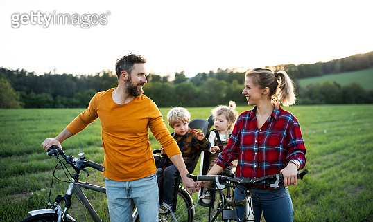 Family with two small children on cycling trip, resting.
