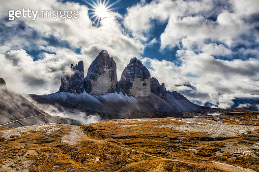 Sunlight on a cloudy day in Dolomites with a view of famous Tre Cime di Lavaredo