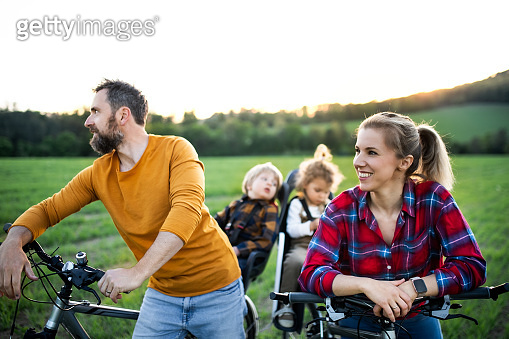 Family with two small children on cycling trip, having fun.