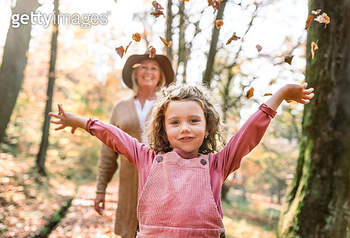 Small girl with grandmother on a walk in autumn forest, having fun.